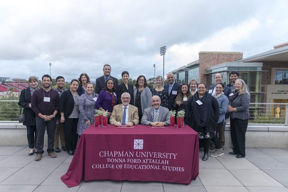 Group of faculty and staff around signing tale