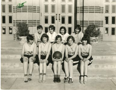Women in vintage uniforms pose for basketball team shot in the 1920s