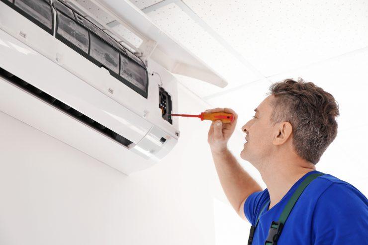Mature electrician repairing air conditioner indoors