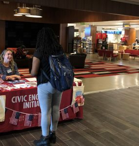 Cydney Hansen '22 helps students register to vote at Civic Engagement's voter registration table on campus this week.