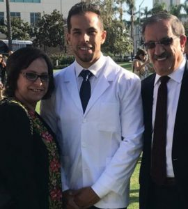 ramsey halim in a white pharmacist coat with his mom and dad to his left and right standing in grass with chapman university buildings behind them.