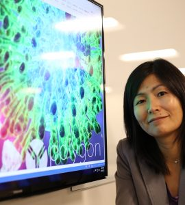 Pharmacy professor Jerika Lam poses next to a screen image of a virus molecule.