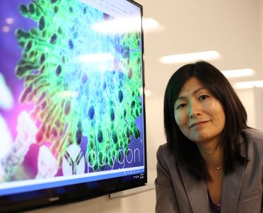 Pharmacy professor Jerika Lam poses next to a screen image of a virus molecule.