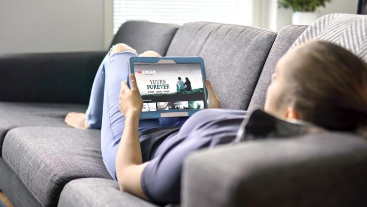 Person laying on couch streaming TV show on tablet.