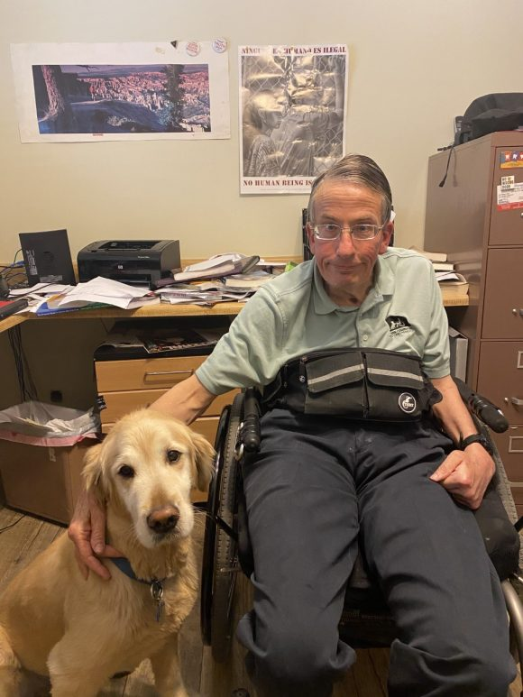 Man who uses a wheelchair next to dog