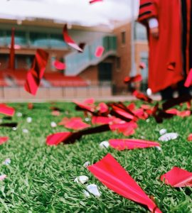 confetti on field with person in academic robes in background