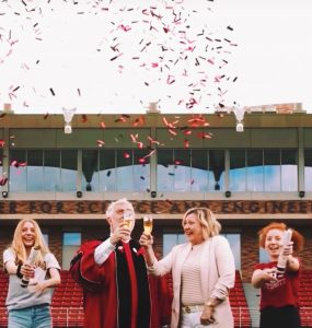 President struppa in robes with wife and daughters and confetti