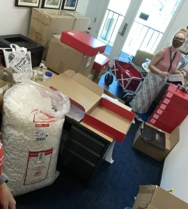 Boxes containing laptops and supplies for new students at Chapman's Fowler School of Engineering are prepped for shipping by two university staff members.