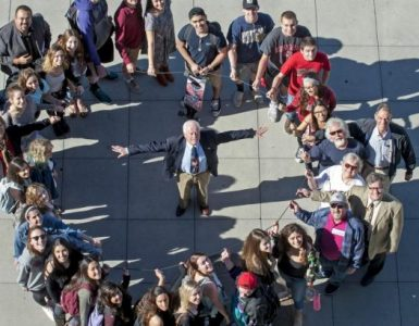 Attendees gather together and pose forming the shape of an O-ring.
