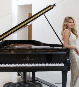 Chapman piano performance alumna Oliva Mellow standing by a baby grand piano.