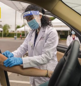 A Chapman University Pharm.D. student administers a seasonal flu shot at one of several drive-through immunization clinics hosted by Chapman.