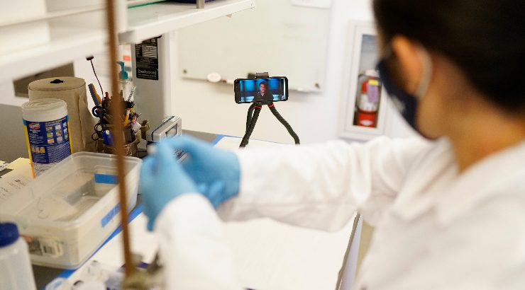 A chemistry student performs lab work as chemistry professor Chris Kim, Ph.D., provides mentorship and supervision through a mounted phone, tripod and body camera.