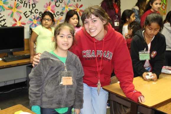 A Chapman student standing with a student from Higher Ground in a classroom.