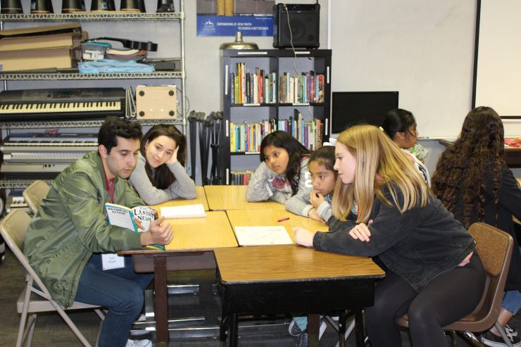 Chapman students seated at a table and reading to students from the community.