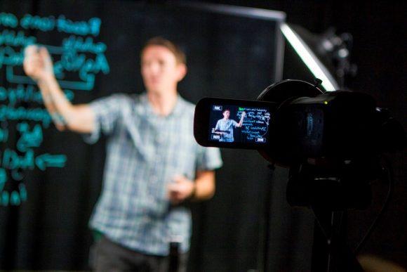 Professor Gartner teaching with a remote video screen.