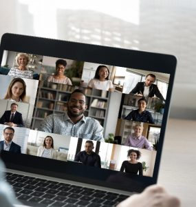 Person in online meeting with various participants.