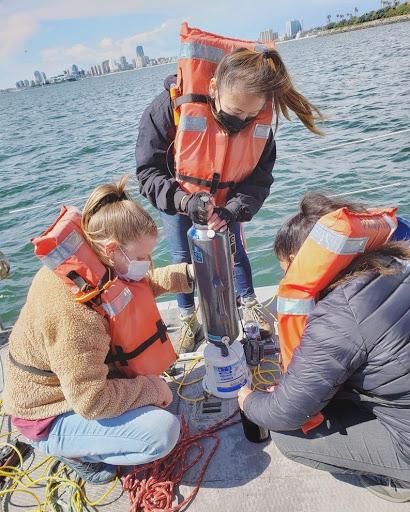 Student Emma Kocik does aquatic resarch on a dock.
