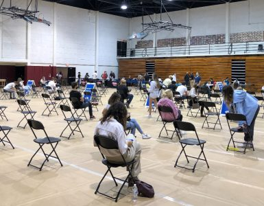 Students sit socially distanced at the Hutton Sports Center.