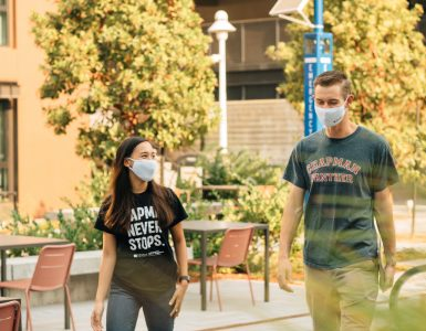 Two chapman students in face masks walking through campus.