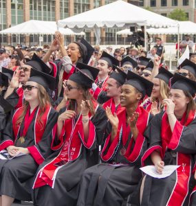 students in black academic gowns, mortar caps and red hoods