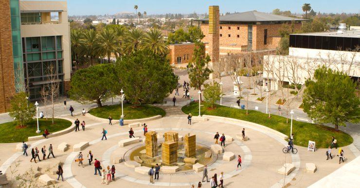 Panoramic view of people walking across Attallah Piazza.