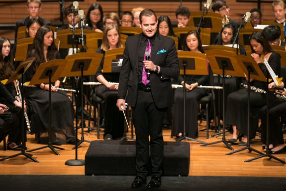 Teren Shaffer conducts wind ensemble during a concert.