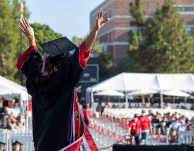 woman in black cap and gown with arms raised as she crosses the stage