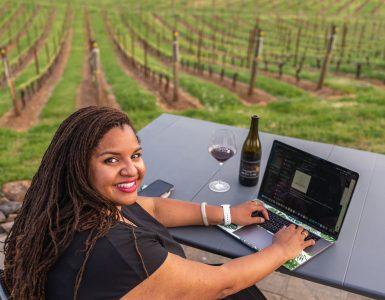 tiquette bramlett at desk overlooking vineyard