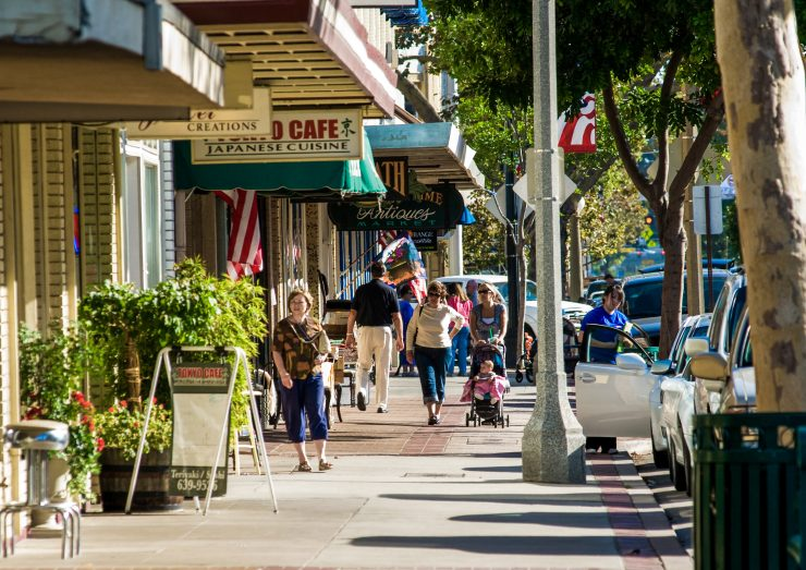 Image of people walking on sidewalk in downtown shopping area