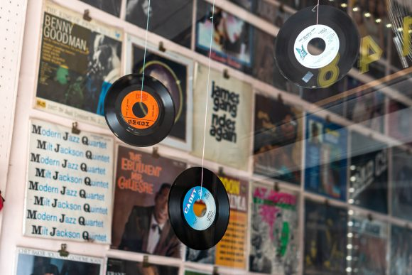 Vinyl records hang in front of a window at an Old Towne Orange music shop.