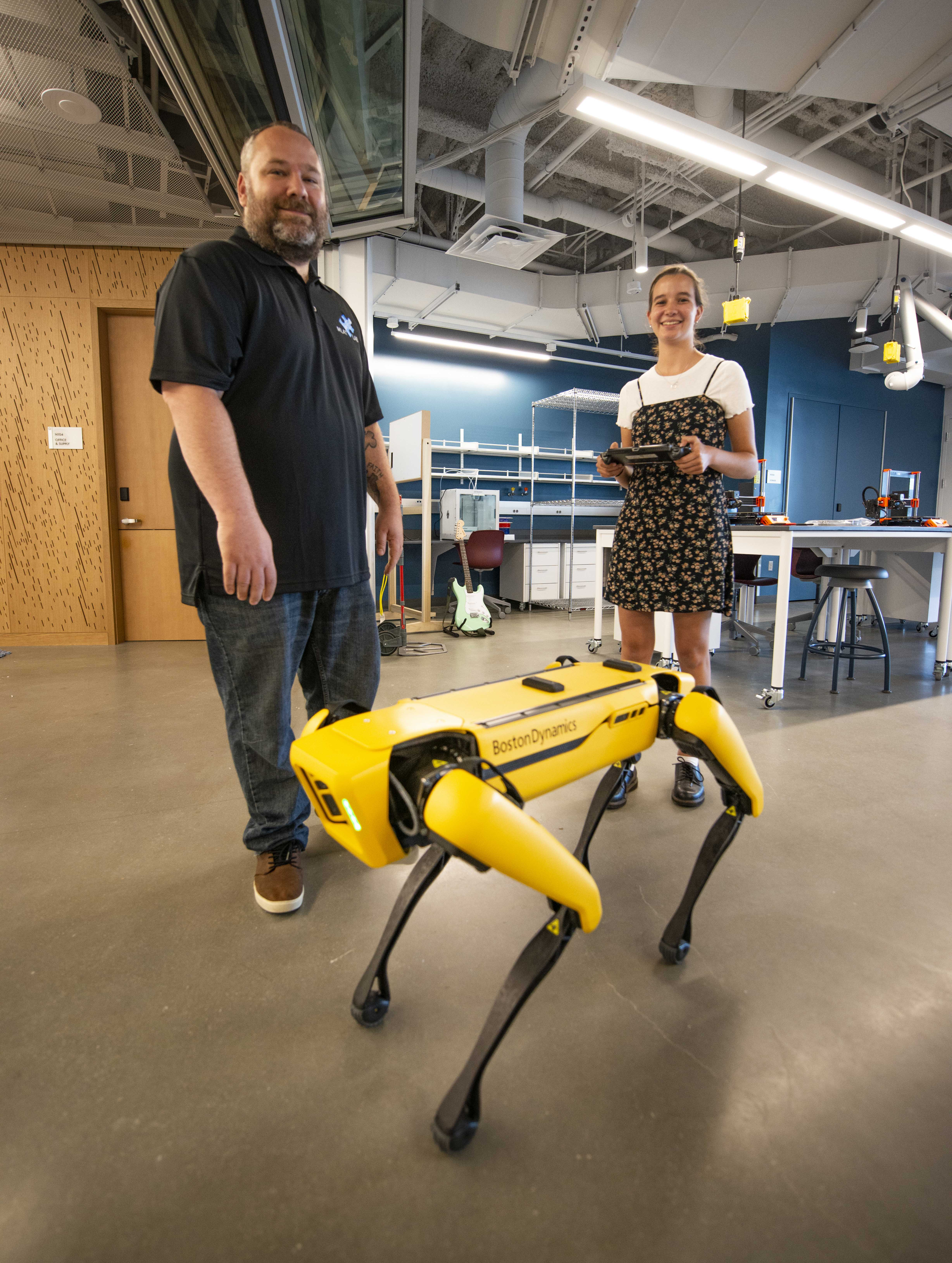 Erik Linstead and student with robot dog.