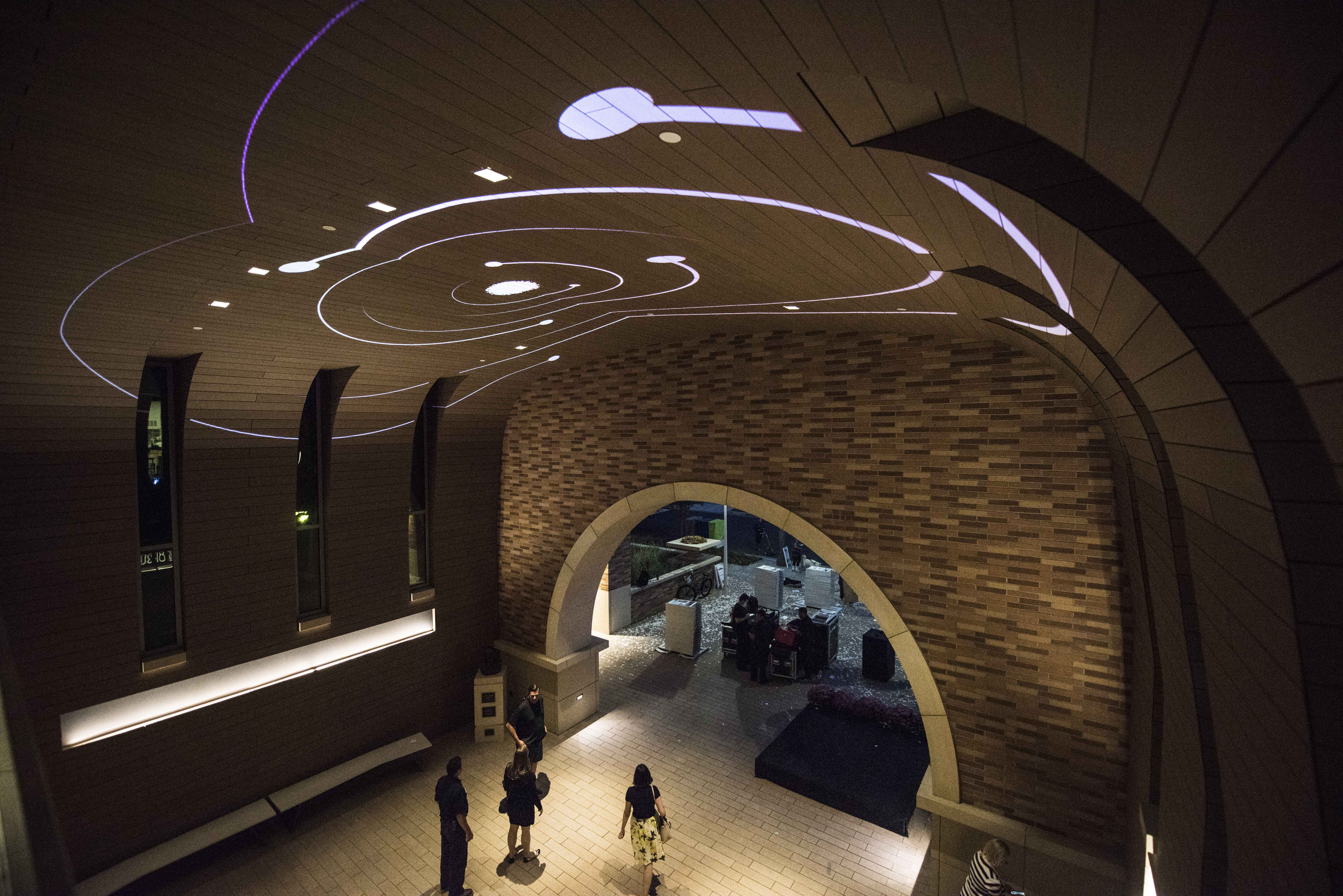 he vaulted ceiling at Keck Center comes to life at night with science-themed projections.